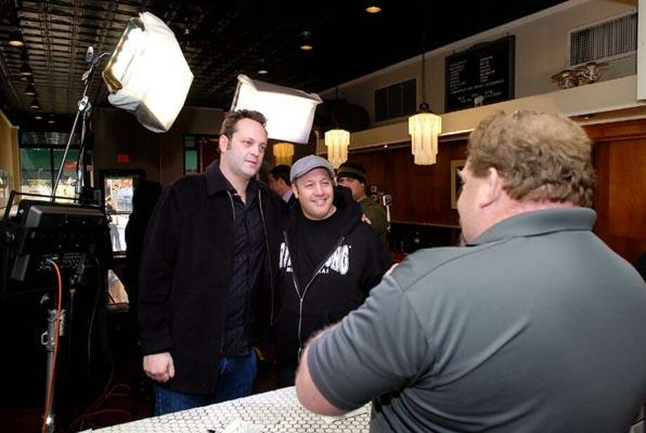 Actors Vince Vaughn, left, and Kevin James pose for a picture for Pepe's Pizza General Manager Steve Adkins after doing television interviews promoting their upcoming movie. (Peter Casolino/Register)