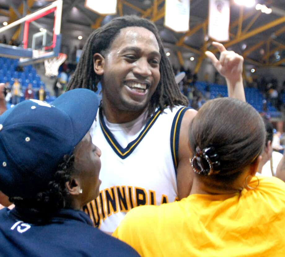 Justin Rutty of Quinnipiac Unversity is mobbed by student fans after defeating  Monmouth College during the second half of the the NEC Tournament quarterfinals Thursday at Quinnipiac University. (Peter Hvizdak/Register Staff)