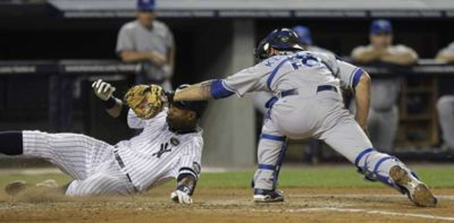 The Yankees' Curtis Granderson slides safely under the tag of Royals catcher Jason Kendall in the sixth inning of New York's 7-1 win on Friday night. (Associated Press/Julie Jacobson) Photo: AP / AP