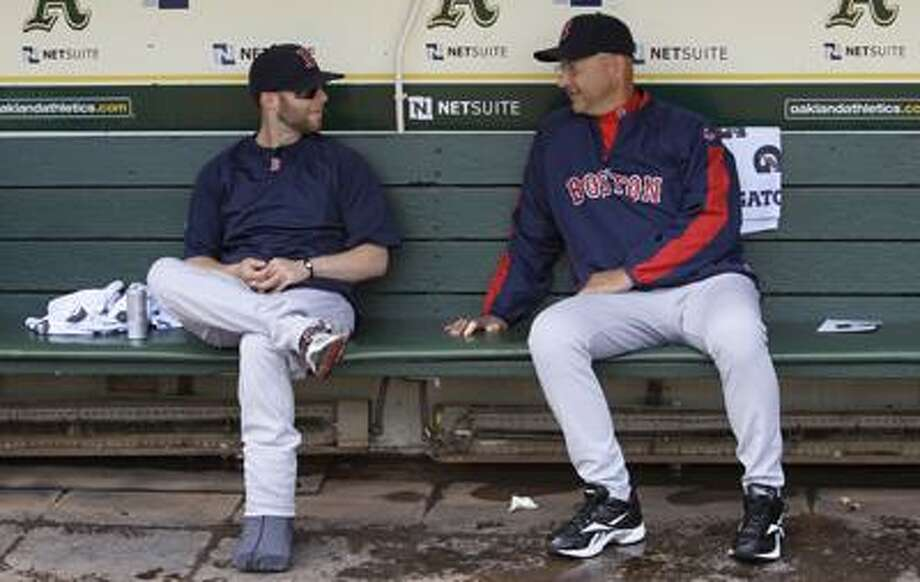 Dustin Pedroia, left, and manager Terry Francona talk in the dugout before a Wednesday's game against the Athletics in Oakland, Calif. (Associated Press/Jeff Chiu) Photo: AP / AP