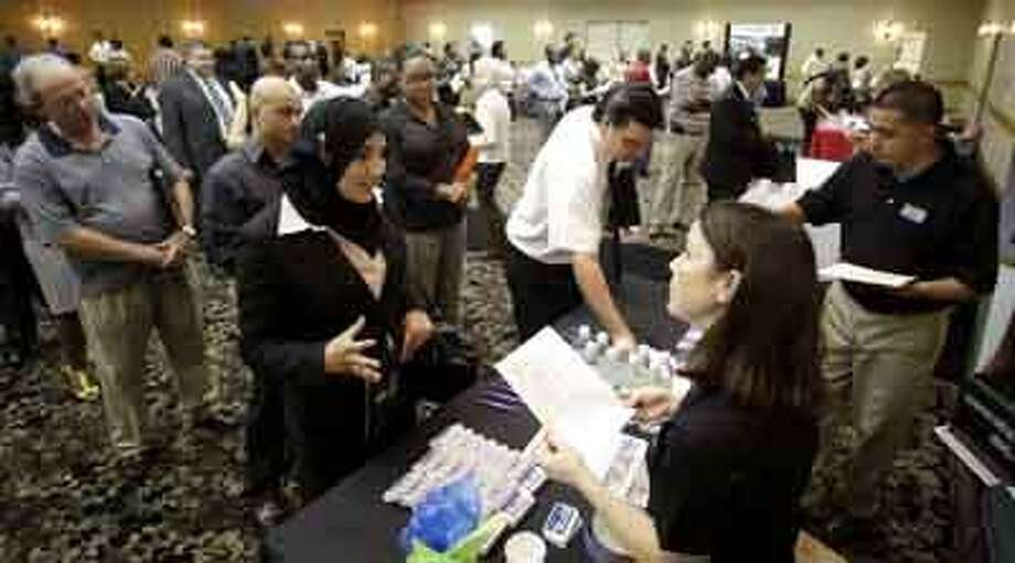 In this July 20, 2010 photo, Saida Laktiri, center left, of Garland, Texas meets with Roni McConachie, front right, a recruiter with EFA Processing during a National Career Fairs Job Fair in Plano, Texas. (AP Photo/Tony Gutierrez) Photo: AP / AP