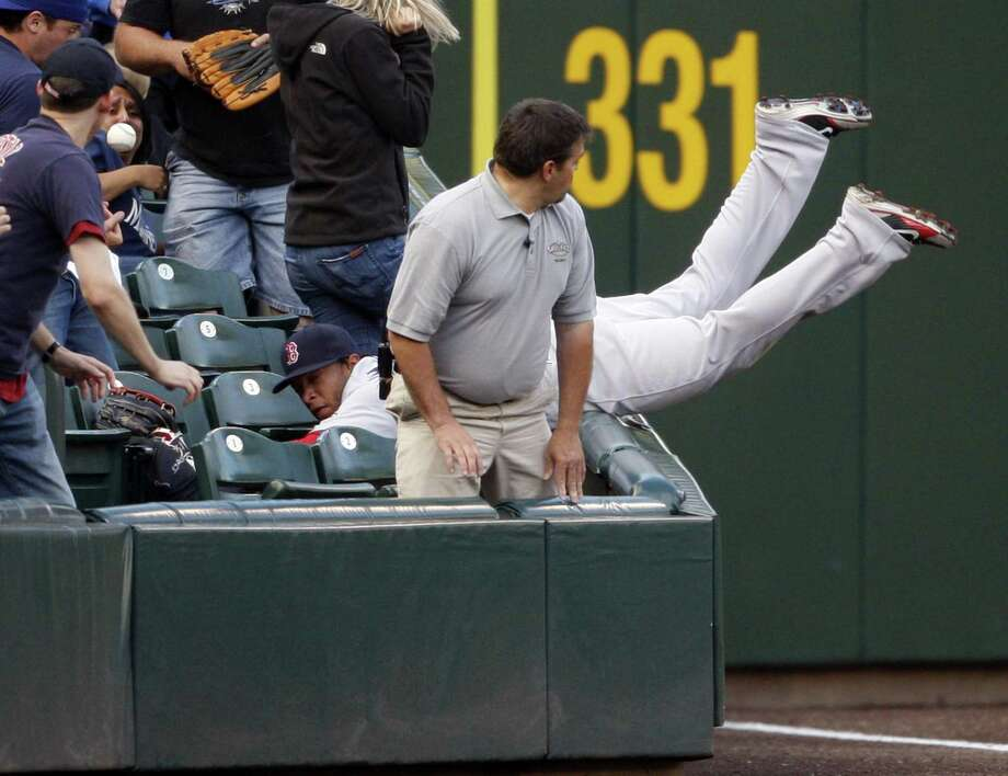 Darnell McDonald falls into the stands attempting to catch a foul ball in the first inning of Boston's 8-6 win over the Mariners Thursday in Seattle. (Associated Press/Kevin P. Casey) Photo: ASSOCIATED PRESS / FR132181 AP