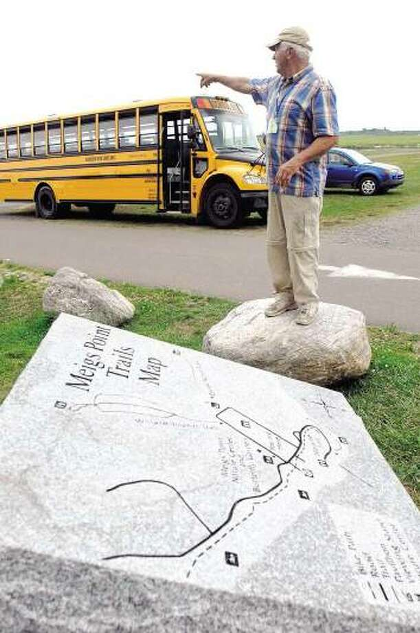 Friends of Hammonasset board member Don Rankin points out various areas mapped on the memorial monument carved in granite in memory of E. Arthur Root III of Madison at Hammonasset Beach State Park's Meigs Point nature center. (Peter Hvizdak/Register)