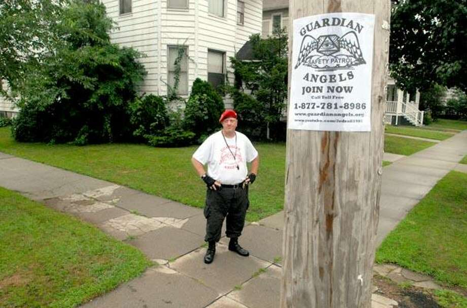 Mark DelGuidice of Norwalk, a member of the New Haven chapter of the Guardian Angels, stands watch Wednesday evening  at the corner of Ellsworth Ave. and Maple Street in New Haven. (PETER HVIZDAK/Register)