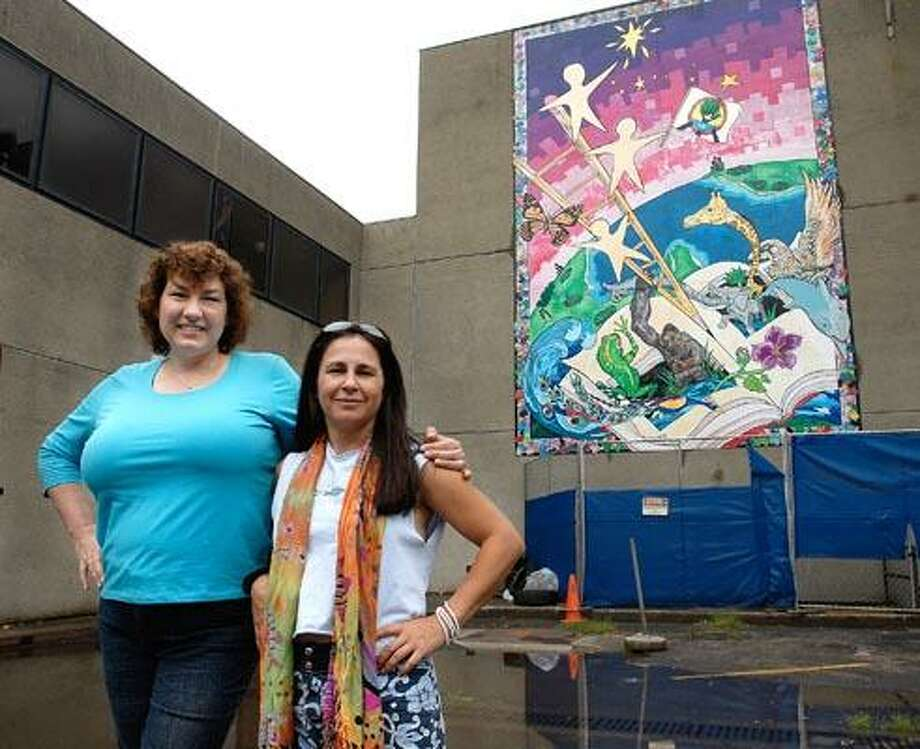 Cas100714 07/14/10 New Haven--East Rock School Art teacher Elizabeth Cassidy, left and artist JoAnn Moran are hoping to save the 12-paneled mural that hangs on the school. -Photo/Peter Casolino