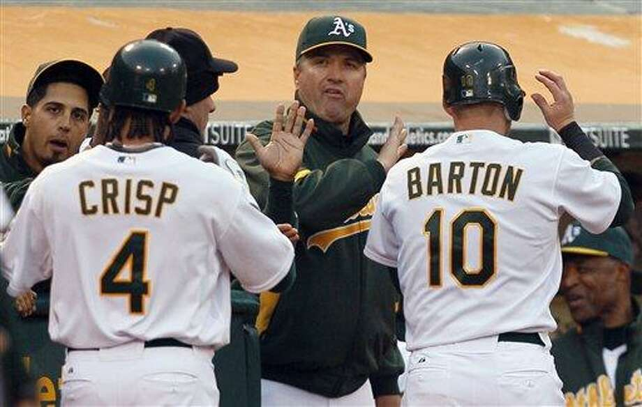Oakland Athletics' Coco Crisp (4) and Daric Barton (10) are congratulated by A's manager Bob Geren, center, after both scored against the Boston Red Sox during the third inning of a baseball game Tuesday, July 20, 2010, in Oakland, Calif. Crisp & Barton scored both scored on a double by Jack Cust. (AP Photo/Ben Margot) Photo: ASSOCIATED PRESS / AP