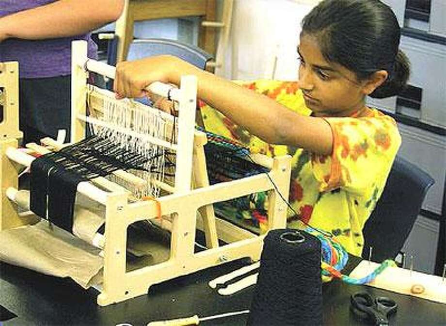 """Kids learn how to weave a """"One-Day"""" scarf in a session taught by master weavers Martha Burns and Myra Serrins. (Contributed)"""