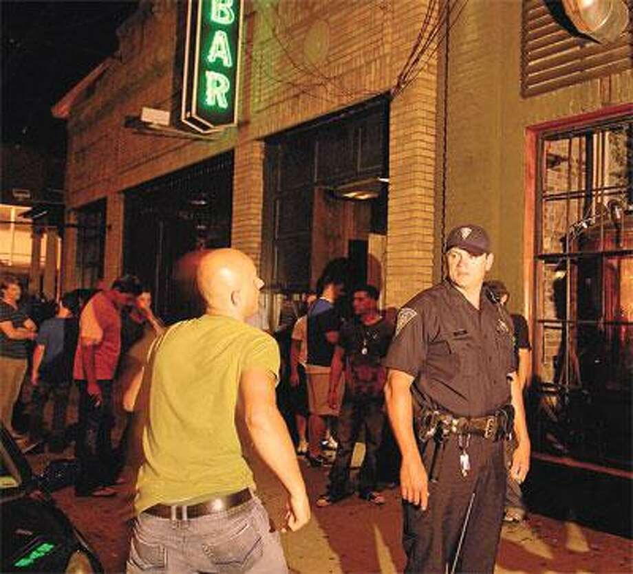 Officer Arpad Tolnay works an extra-duty job in front of Bar on Crown Street in New Haven. (Peter Hvizdak/Register)