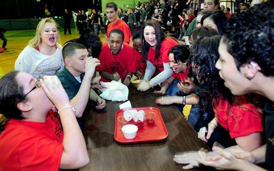 """The sophomore class at Emmett O'Brien Regional Technical High School in Ansonia cheers on classmates Jordan Morgan, 15, far left, and Steven Jimenez, 16, third from left, in the Jell-O-eating contest during the """"Class Wars"""" competition at the school Thursday. (Photo by Arnold Gold)"""