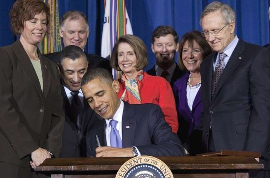 """Lawmakers and supporters look on as President Barack Obama signs """"don't ask, don't tell"""" repeal legislation that would allow gays to serve openly in the military, Wednesday, Dec. 22, 2010, at the Interior in Washington.  (AP Photo/Evan Vucci) Photo: AP / AP"""