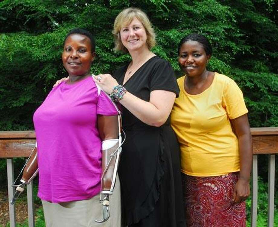Martha Hoffman, founder of Call to Care Uganda, center, stands with Jonas Tumuhebwe, left, and Jolly Kabigumira, right. Tumuhebwe has received prosthetic arms with the help of Hoffman's organization. (Brad Horrigan/Register)