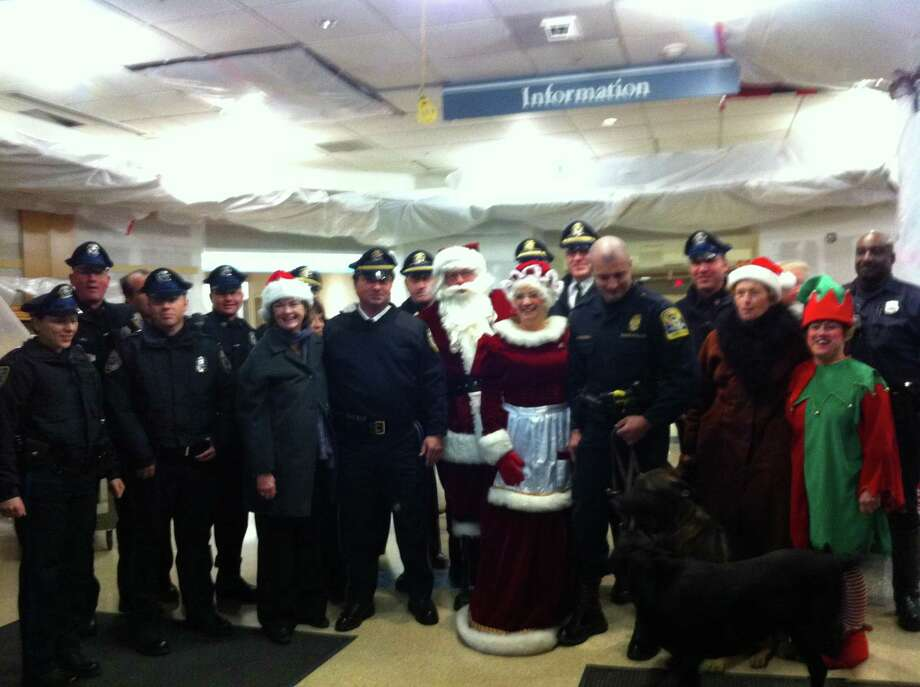Left to right, Madison Officers Patricia Alonso; Tom Bull; Joe Race; Christine Dowling (Y-NHH); Chief John Drumm; Sgt. Jon Pardo; Santa; Mrs. Claus, Lt. Allen Gerard; Trooper Tory Marsden and K-9; Officer Phil Rosati; an unidentified Y-NHH staff member; Elf Marianne. (Alexandra Sanders/Register)