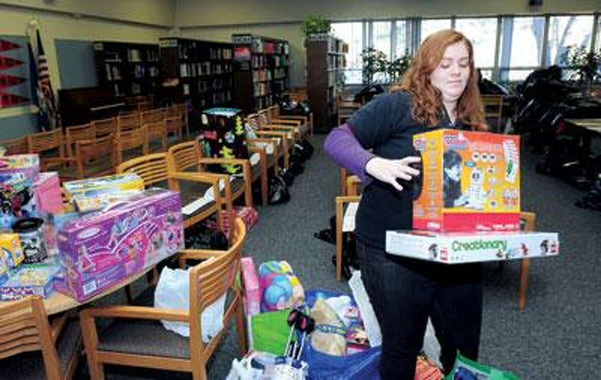 Brianna Paolillo, 16, sorts out donated gifts for a toy and clothing drive in the library at Platt Regional Vocational Technical School in Milford on Friday. (Arnold Gold/Register)
