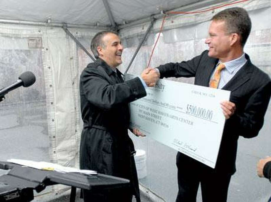 West Haven Mayor John Picard, left, shakes hands in 2009 with Michael Morand, associate vice president of New Haven & State Affairs at Yale University, after being presented a check for $500,000 to renovate the Masonic Temple on Center Street in West Haven. The city has received two more grants for $30,000 for the project. (Arnold Gold/Register)