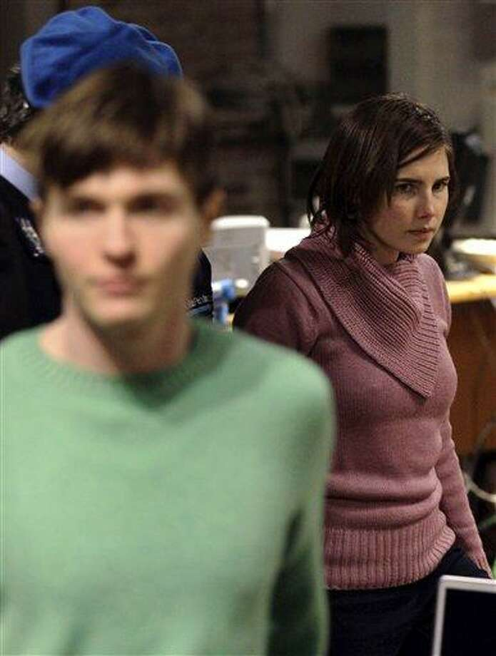 Convicted U.S. student Amanda Knox, right, walks past Raffaele Sollecito, as she arrives after a break to attend a hearing in her appeals trial, at Perugia's courthouse, Italy, Saturday, Dec. 18, 2010. An Italian court hearing the appeals murder trial of Amanda Knox was deliberating Saturday whether to allow new witnesses and an independent review of evidence - a crucial decision for the defense of the American student convicted of killing her British roommate. Her co-defendant and ex-boyfriend, Sollecito of Italy, was convicted of the same charges and sentenced to 25 years. (AP Photo/Alessandra Tarantino) Photo: AP / AP