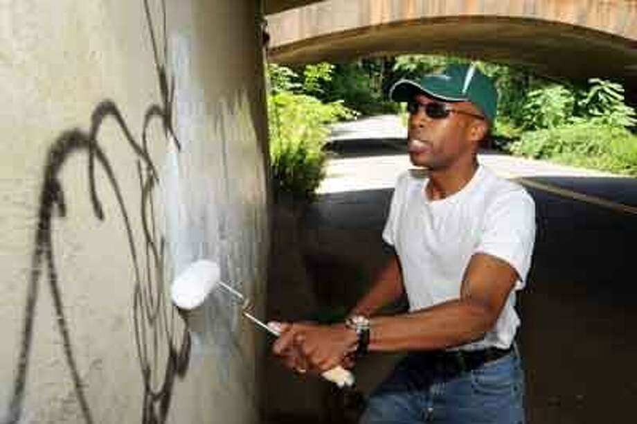 Hamden Mayor Scott Jackson paints over graffitti at on underside the Rt 15 overpass located at Wintergreen ave near Carbonella Dr. 07/12/10 VM Williams/Register
