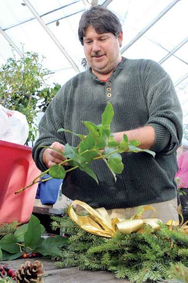 Scott Hickman, supervisor of the Greenbrier Greenhouse Program at Edgerton Park in New Haven prepares a Christmas wreath at the program's greenhouse. (VM Williams/Register)