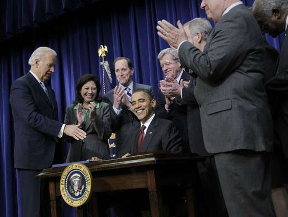 President Barack Obama, center seated, smiles after signing the $858 billion tax deal into law in a ceremony in the Eisenhower Executive Office Building on the White House complex, Friday, Dec. 17, 2010 in Washington. (AP Photo/Pablo Martinez Monsivais) Photo: AP / AP