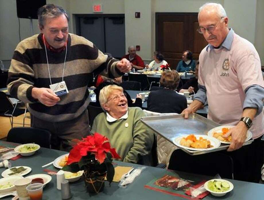 The 30th Annual Guilford Rotary Holiday Senior Luncheon was held at Guilford's Nathaneal Greene Community Center. This year it served about 200. David Vail left and John Murphy right serve Beatrice Armstead center. (Mara Lavitt/New Haven Register)