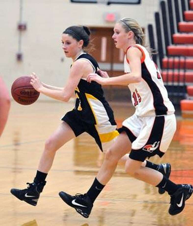 Shelton-- Hand's Kara McHugh drives up the court as Shelton's Megan Burk defends during the first period.  Photo by Peter Casolino/New Haven Register12/17/10 Cas101217