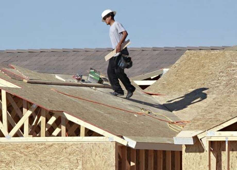 In this Nov. 30, 2010 photo, a construction worker  angles his way across the roof of a house, in Gilbert, Ariz. The National Association of Home Builders said Wednesday, Dec. 15, 2010, its housing market index held steady in December, with many respondents feeling uncertain about the prospect for improved home sales in the near future. (AP Photo/Matt York) Photo: AP / AP