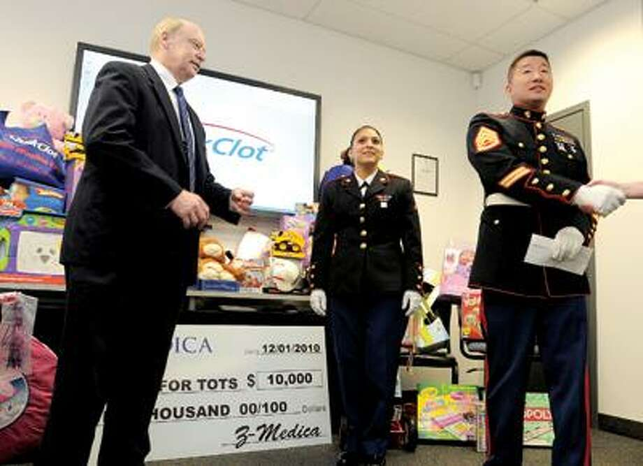 Marine Staff Sgt. Chihwan Kim, right, accepts a check for $10,000 from Z-Medica CEO Brian Herrman for the Marine Toys for Tots Foundation. Center is Pvt. Karen Meza. (Brad Horrigan/Register)