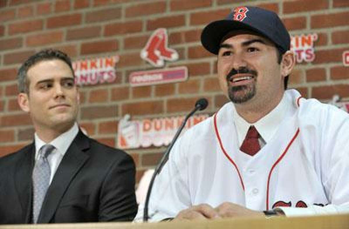 New Boston Red Sox first baseman Adrian Gonzalez, right, speaks to reporters as Red Sox General Manager Theo Epstein, left, looks on during a news conference at Fenway Park in Boston, Monday, Dec. 6, 2010. The Red Sox finally landed the All-Star first baseman, acquiring him from the San Diego Padres in exchange for three prospects and a player to be named later. (AP Photo/Josh Reynolds)