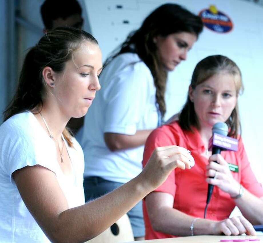 Anastasia Pavlyuchenkova (left) and WTA tour supervisor Melanie Tabb (right) begin the women's draw at the Pilot Pen tennis tournament in New Haven on 8/20/2010.  At center is assistant Brittany Allen.Photo by Arnold Gold   AG0382B