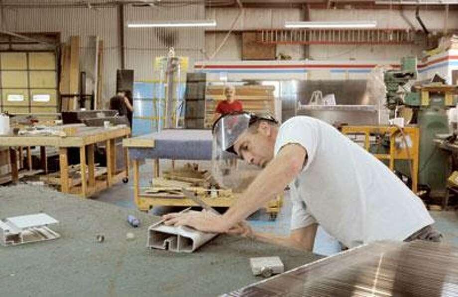 Technician Eric Valentino works on a piece of sample material. (Melanie Stengel/Register)