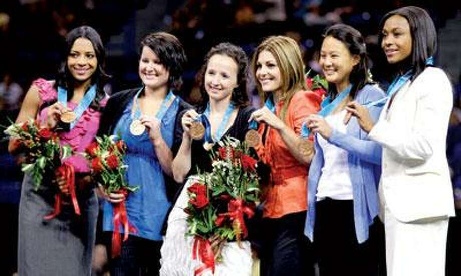 United States' gymnasts from the Sydney Olympics hold up their bronze medals following a ceremony in Hartford Wednesday. The U.S. women's team received the third-place medals that were stripped from China because a member of that team was found to be underage. From left to right, are: Tasha Schwikert, Elise Ray, Kristin Maloney, Jamie Dantzscher, Amy Chow and Dominique Dawes. (Associated Press)