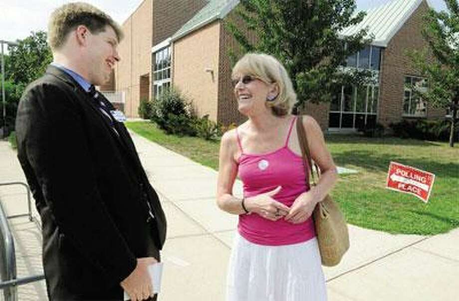 New Haven Alderman Roland Lemar, left, Democratic candidate for the state House in the 96th District, talks with Hamden voter Susan Gallagher after she voted at Spring Glen School Tuesday. She said Lemar got her vote when he came to her door campaigning on the hottest day of the summer. (Melanie Stengel/Register)