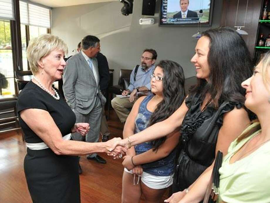 Linda McMahon greets Alison Velez, owner of LuDal's Restaurant in North Haven. On the left is Gabriella Velez (her daughter) and Gina Camarota the restaurant manager. (Peter Casolino/Register)