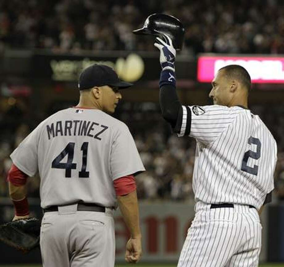 Boston Red Sox first baseman Victor Martinez (41) watches as New York Yankees Derek Jeter tips his cap to the crowd after hitting his 2,874th hit, a second-inning, RBI single, surpassing Babe Ruth on Major League Baseball's all time hits list, in their baseball game at Yankee Stadium on Sunday, Aug. 8, 2010 in New York. (AP Photo/Kathy Willens) Photo: AP / AP