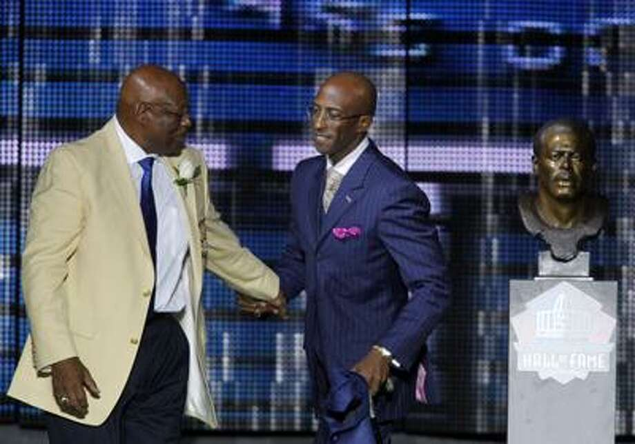 Former Hillhouse High and Denver Broncos running back Floyd Little, left, walks with his son, Marc, during Floyd's enshrinement in the Pro Football Hall of Fame Saturday in Canton, Ohio. (Associated Press/Ron Schwane) Photo: AP / FR78273 AP