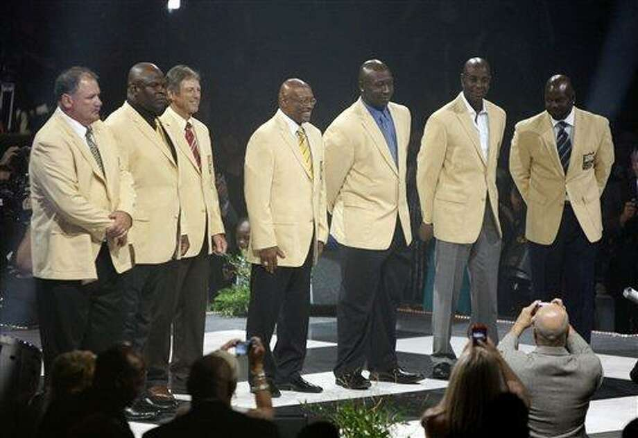 The Pro Football Hall of Fame Class of 2010 gather for the first time with their gold blazers that were presented to them at the Hall of Fame Festival Enshrinees Dinner at the Canton Civic Center Friday, Aug. 6, 2010 in Canton, Ohio. From left are: Russ Grimm, Rickey Jackson, Dick LeBeau, Floyd Little, John Randle, Jerry Rice and Emmitt Smith. The seven NFL greats will be inducted into the Pro Football Hall of Fame Saturday. (AP Photo/Scott Heckel) Photo: AP / The Repository