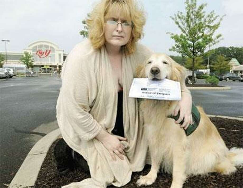 Kim Mucha of Wallingford poses with her dog, Ivy, outside the Big Y Supermarket in North Haven Thursday. In Ivy's mouth is the Notice of Trespass Mucha received after the service dog defecated in the store in late June. (Mara Lavitt/Register)