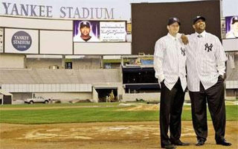 The Yankees' latest free-agent acquisitions, pitchers A.J. Burnett, left, and CC Sabathia pose for photographers on Thursday while standing on the field at the new Yankee Stadium that they will call home next season. (Associated Press)