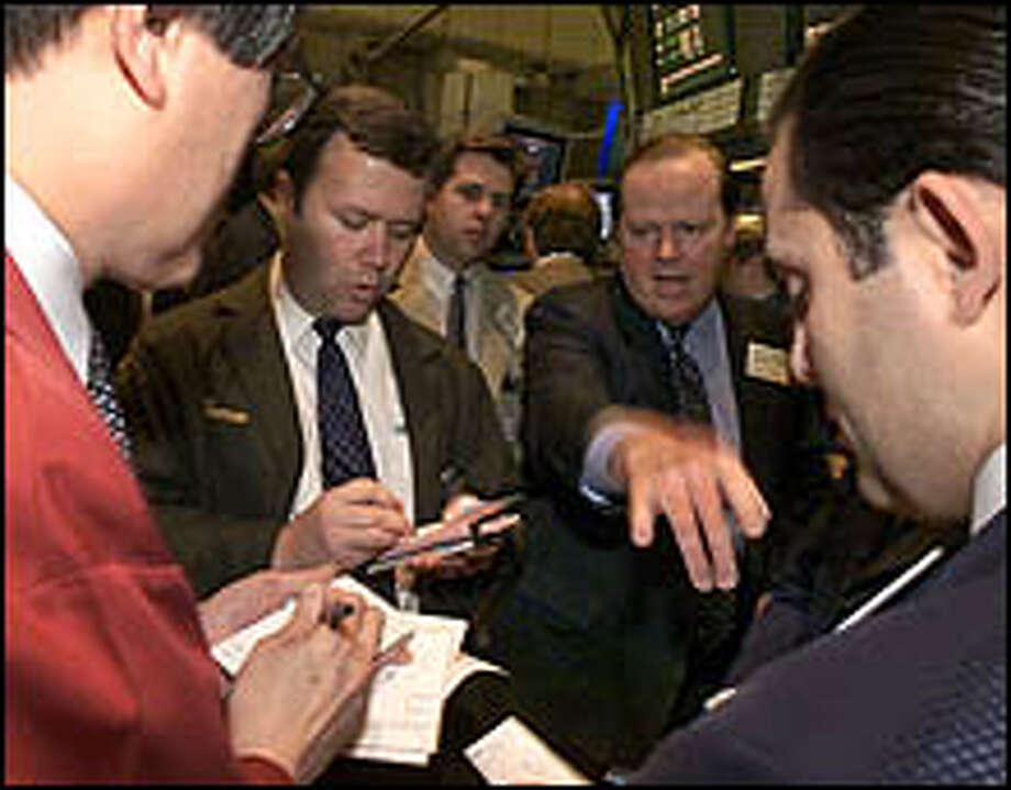 Specialist Donald Foley, second from right,  conducts trading in shares of Chase Manhattan Bank on the floor of the New York Stock Exchange, Thursday March 23, 2000. Stocks moved broadly higher today, led by another advance in high-tech issues, as Microsoft surged on hopes that the software maker and the government may soon resolve their longstanding antitrust case. (AP Photo/Richard Drew) Photo: AP / AP