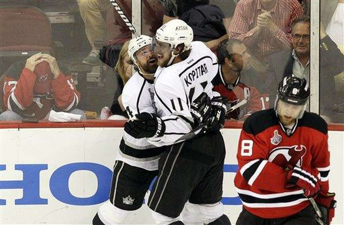 Los Angeles Kings' Anze Kopitar (11), of Slovenia, celebrates with teammate Justin Williams after scoring the game-winning goal during the overtime period of Game 1 of the NHL hockey Stanley Cup finals as New Jersey Devils' Dainius Zubrus (8), of Lithuania, skates away, Wednesday, May 30, 2012, in Newark, N.J. The Kings won 2-1. (AP Photo/Frank Franklin II)