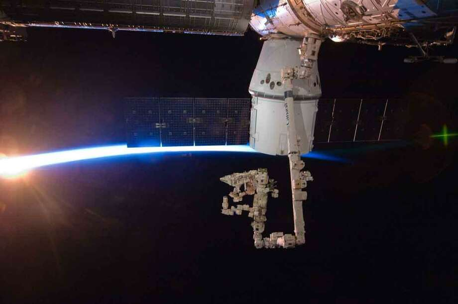 In this image provided by NASA with rays of sunshine and the thin blue atmosphere of Earth serving as a backdrop, the SpaceX Dragon commercial cargo craft is berthed Sunday to the Earth-facing side of the International Space Station's Harmony node. Associated Press Photo: ASSOCIATED PRESS / AP2012