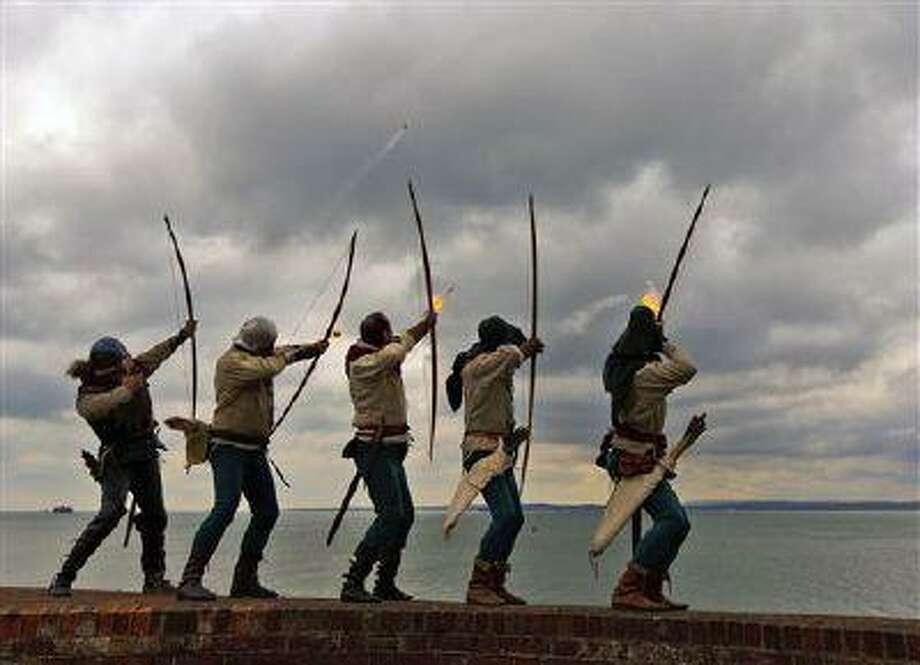 Archers of the Purbrook Bowmen, dressed in Tudor looking clothes, fire a volley of flaming arrows from Southsea Castle into The Solent, towards where the Mary Rose sank in 1545, at Portsmouth on the south coast of England, Thursday May 30, 2013. Henry VIII's flagship sank during a battle against the French navy and was raised from the seabed in 1982. The ceremony was one of the events to mark the opening of the new Mary Rose Museum at Portsmouth Historic Dockyard. In the background, left, is one of the Solent Forts, and at right is part of the Isle Of Wight. (AP Photo / Chris Ison, PA) UNITED KINGDOM OUT, NO SALES, NO ARCHIVE Photo: AP / PA