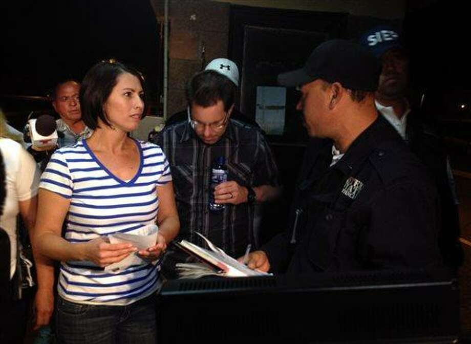 Yanira Maldonado, 42, left, accompanied by her husband, Gary, center, speaks to an official after being released from a prison on the outskirts of Nogales, Mexico late Thursday, May 30, 2013. Maldonado, jailed in Mexico on a drug-smuggling charge, was released after court officials reviewed her case. She was arrested by the Mexican military last week after they found nearly 12 pounds (5.4 kilograms) of pot under her seat on the commercial bus traveling from Mexico to Arizona. (AP Photo/Cristina Silva) Photo: AP / AP