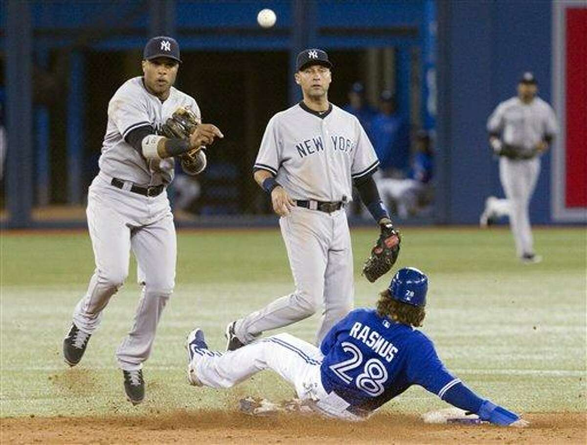 New York Yankees Robinson Cano, left, throws to first as Toronto Blue Jays Colby Rasmus is forced out at second on a double play as Derek Jeter, center, looks on during ninth inning of a baseball game in Toronto on Sunday, Sept. 30 , 2012. (AP Photo/The Canadian Press, Chris Young)