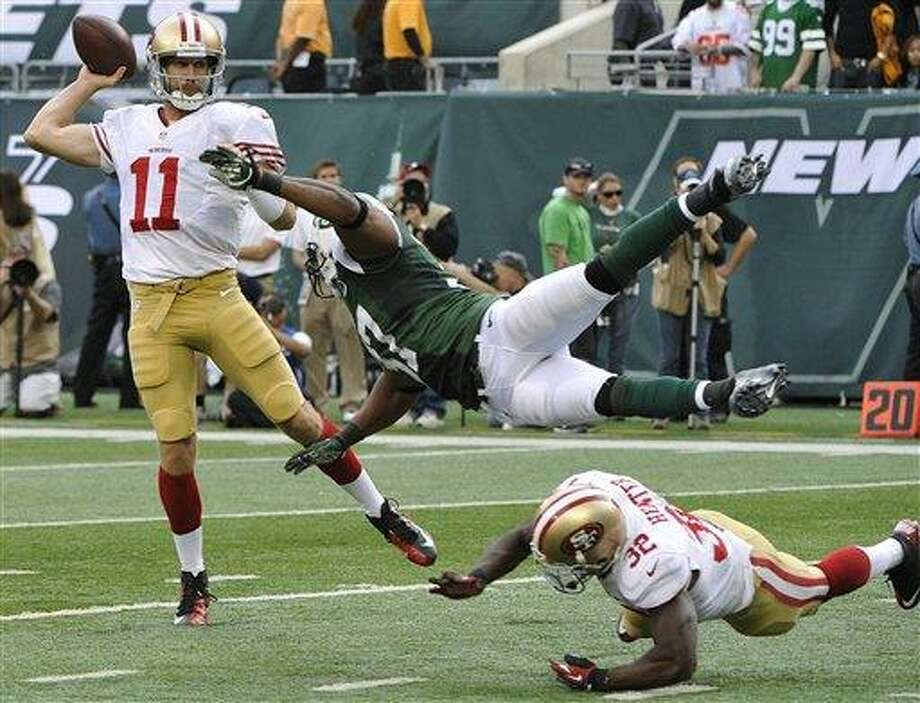 San Francisco 49ers quarterback Alex Smith (11) thows a pass away from New York Jets' Yeremiah Bell (37) as teammate  Kendall Hunter (32) blocks during the second half of an NFL football game Sunday, Sept. 30, 2012, in East Rutherford, N.J. the 49ers won the game 34-0. (AP Photo/Bill Kostroun) Photo: ASSOCIATED PRESS / AP2012