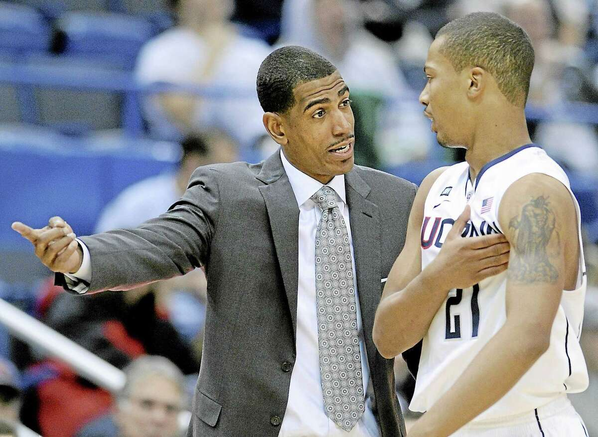 Connecticut coach Kevin Ollie, left, talks with Omar Calhoun during the second half of their team's 61-53 victory over Washington in an NCAA college basketball game in Hartford in December 2012. Ollie will speak at the Middlesex County Chamber of Commerce breakfast in October.