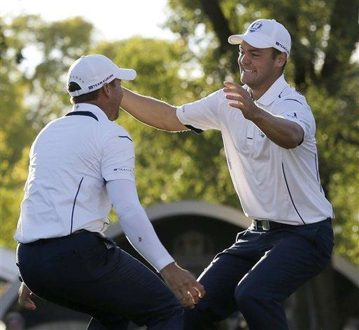 Europe's Martin Kaymer leaps into the arms of teammate Sergio Garcia after winning the Ryder Cup PGA golf tournament Sunday, Sept. 30, 2012, at the Medinah Country Club in Medinah, Ill. (AP Photo/David J. Phillip)