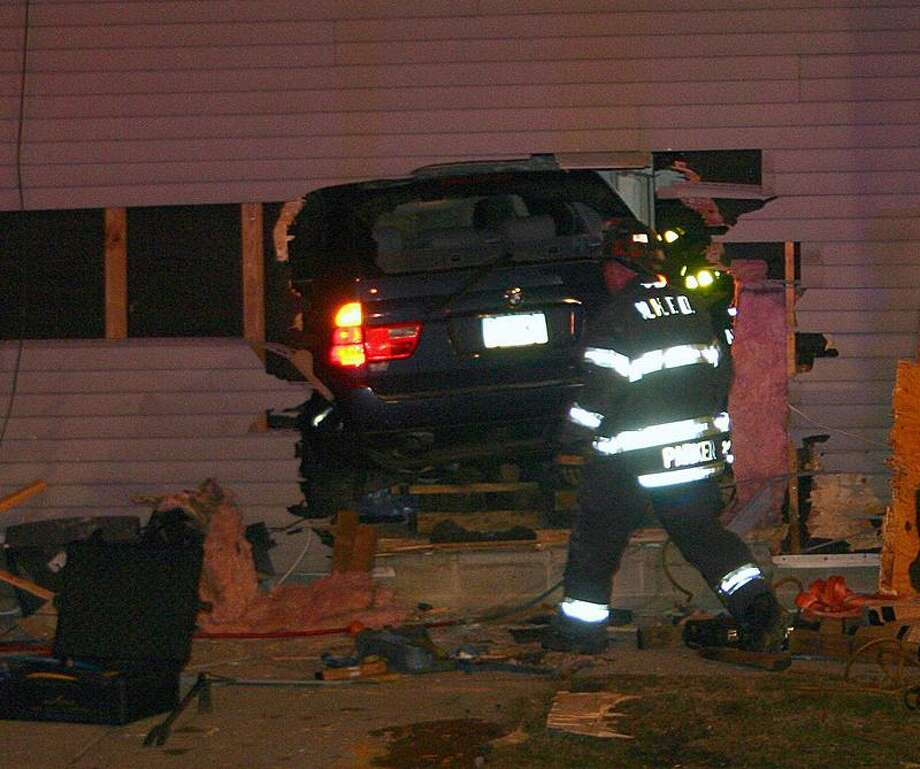 New Haven firefighters work frantically to free a man who was trapped under an SUV as he was sleeping in his bedroom. The vehicle crashed through the house at the corner of Winchester Avenue and Compton Street as it was being chased by police. The driver of the vehicle fled the scene and was still being sought by police. (William Kaempffer/New Haven Register)