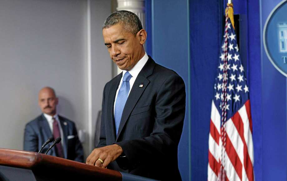President Barack Obama prepares to make a statement on the ongoing budget battle from the Brady Press Briefing Room at the White House in Washington, Monday, Sept. 30, 2013. Obama is ramping up pressure on Republicans to avoid a post-midnight government shutdown. He says a shutdown would hurt the economy and hundreds of thousands of government workers. (AP Photo/Susan Walsh) Photo: AP / AP
