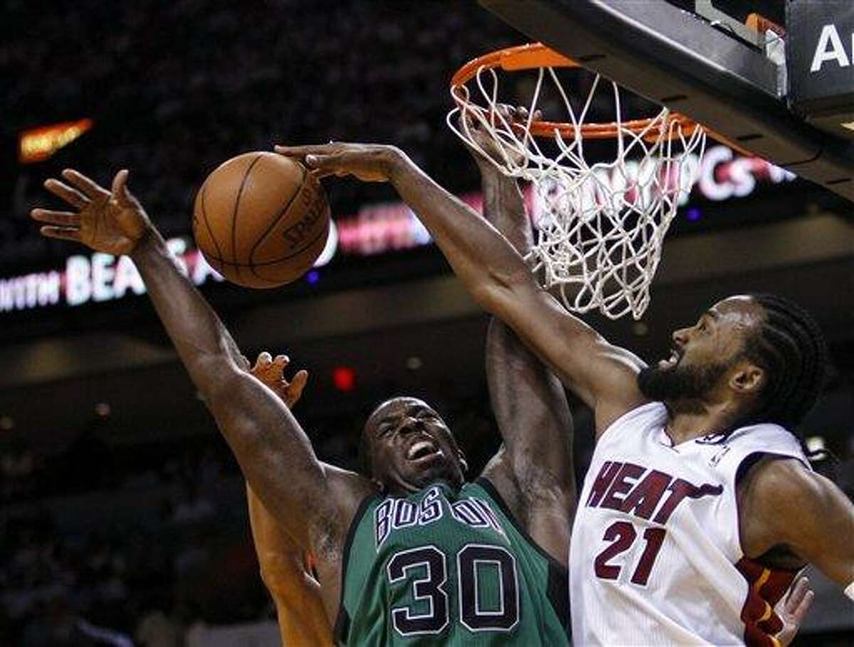 Miami Heat's Ronny Turiaf (21) blocks a shot by Boston Celtics' Brandon Bass (30) during the second half of Game 1 in their NBA basketball Eastern Conference finals playoffs series, Monday, May, 28, 2012, in Miami. (AP Photo/Lynne Sladky)