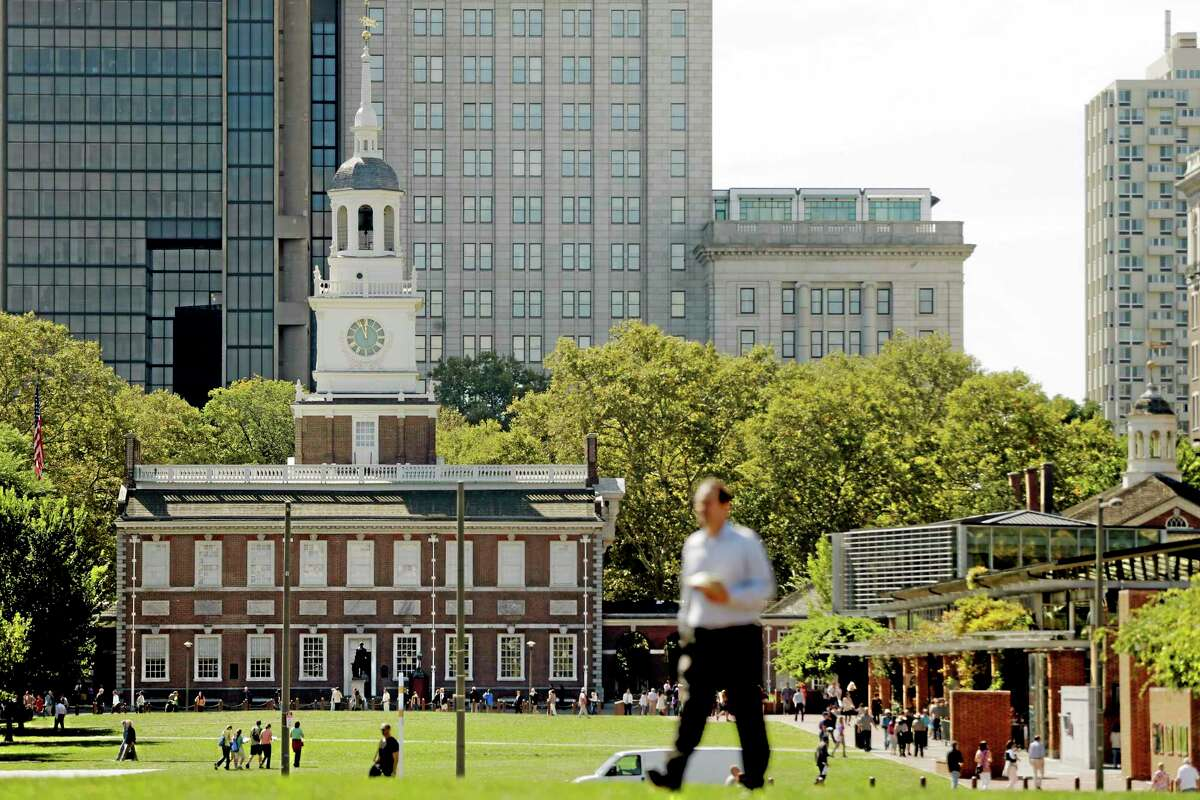 A man walks past Independence Hall at Independence National Historical Park in Philadelphia, Monday, Sept. 30, 2013 as the government teeters on the brink of a partial shutdown at midnight unless Congress can reach an agreement on funding. A conservative challenge to President Barack Obama's cherished health care law pushed the federal government to the brink of a partial shutdown Monday, with the Senate expected to convene just hours before a deadline to pass a temporary spending bill. If no compromise can be reached by midnight, Americans would soon see the impact: National parks would close. (AP Photo/Matt Rourke)